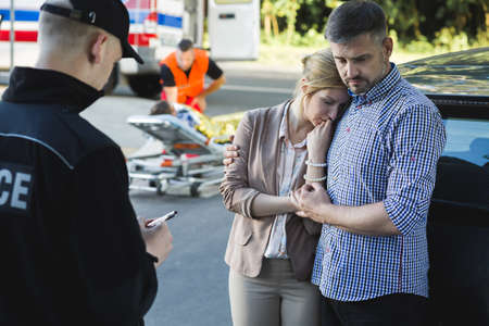 casualty: Anxious parents of an accident casualty talking with the police