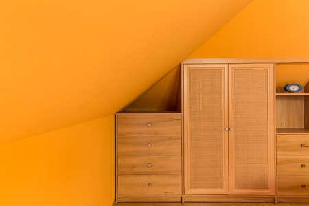 attic room: Image of orange attic room with simple wooden furniture