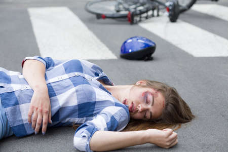 young fellow: Young woman lying hurt on the road with her bike and helmet at the background