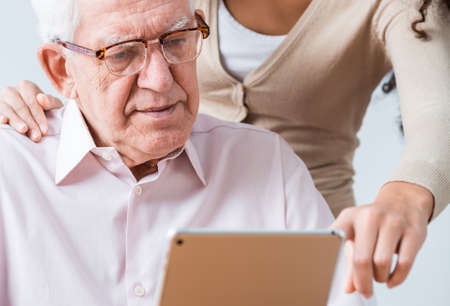 poor eyesight: Young woman helping elderly man with glasses to read questionnaire Stock Photo