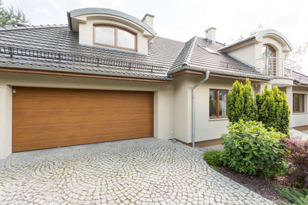 Exterior view of a new villa with garage and cobblestone pathway