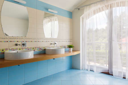 basins: Spacious bathroom with blue and white tiles, two countertop basins, two mirrors and balcony doors