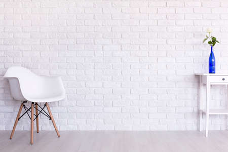 clearness: White chair and table with blue vase on the background of a white brick wall