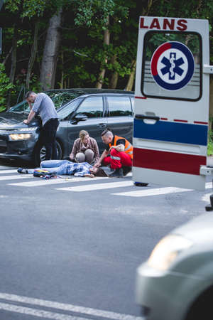 rescuer: Emergency rescuer giving the first aid to the victim of an accident