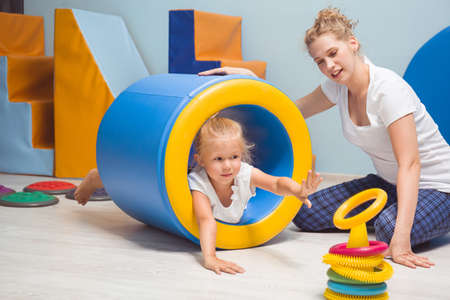Young blonde girl lying in the cylindrical mattress Stockfoto