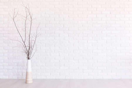 clearness: Vase with branches with white flowers on the background of brick white wall Stock Photo
