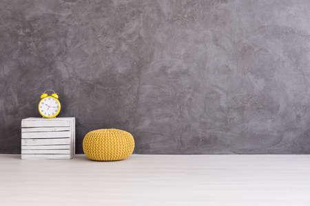 case moderne: pouf gialla e orologio su una scatola di legno su uno sfondo di un muro di cemento grigio Archivio Fotografico