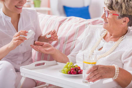 home keeping: Smiled nurse preparing the dose of daily pills to senior patient Stock Photo