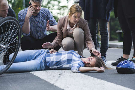 onlooker: Man calling the emergency and woman bending over the accident casualty Stock Photo