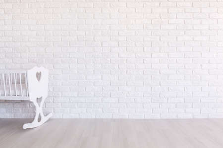 clearness: White cradle on the background of a white brick wall Stock Photo