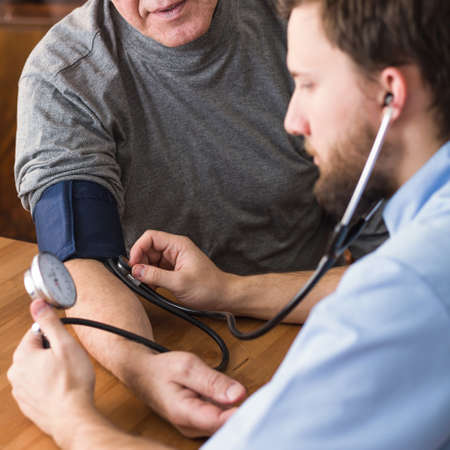 hand cuff: Male patient with hypertension in cardiologists office Stock Photo