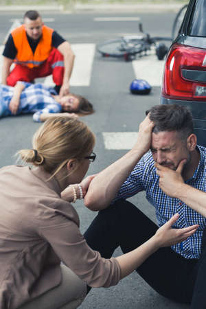 shunt: Crying man sitting on the street with the rescue action behind him Stock Photo