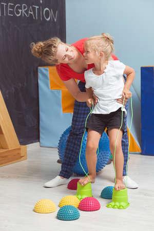 Chica caminando descalzo sobre esteras hemisféricas con la ayuda del terapeuta