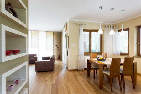 open floor plan: Modern open floor plan interior in beige and brown with dining set and living room furniture set