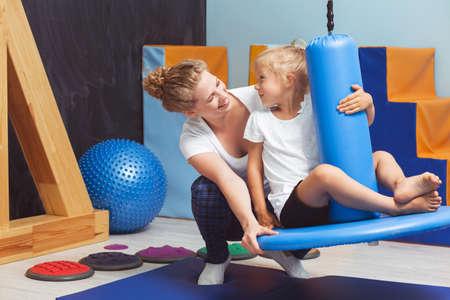 Junge Physiotherapeuten das Mädchen auf einem blauen Schaukel seesawing Lizenzfreie Bilder