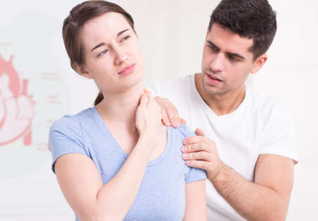 range of motion: Photo of a young woman in pain, having her shoulder rehabilitated by a handsome PT