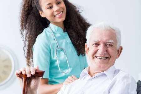 happy seniors: Smiling old man with walking stick and young female caregiver