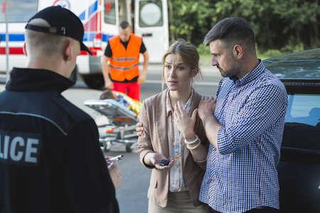 경찰관에게 사고의 장면을 묘사하는 방관자들 스톡 콘텐츠