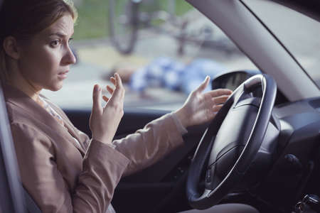 shunt: Frightened woman sitting behind the wheel in place of a crash Stock Photo