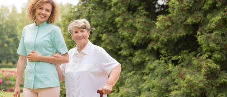 杖と屋外の女性介護者高齢者