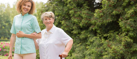 infirm: Elderly with walking stick and female caregiver outdoor Stock Photo