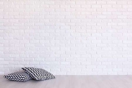 clearness: Two pillows in geometric pattern on the background of a white brick wall Stock Photo