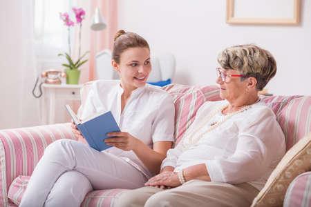 enfermera joven que lee un libro para mujer de más edad que se sientan cerca Foto de archivo