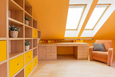 attic room: New design attic room in orange with wall shelving unit, desk and armchair
