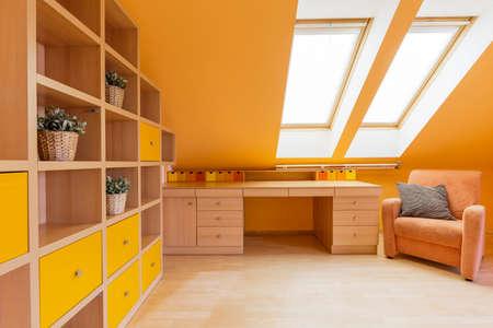 Nieuw design zolderkamer in oranje met muur rekken unit, bureau en een fauteuil