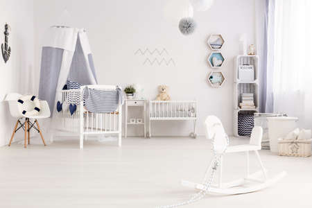 Airy baby room agganged in white and navy blue, with marine decorations Banque d'images