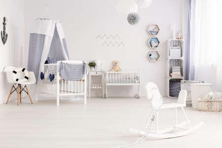 Luchtige babykamer agganged in wit en marineblauw, met mariene decoraties Stockfoto