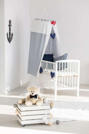 panelled: Cosy corner of a little boys room with wooden box table and a canopy cot in marine style