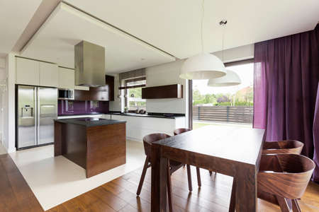 wood flooring: Modern open floor apartment with wooden dining set and functional kitchen with island