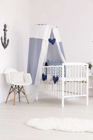 navy blue: Navy blue decorated canopy crib next to a white chair in the corner of a very bright baby room