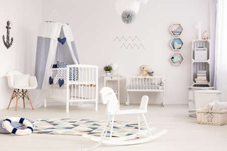 Unique infant room with marine decorative elements and a white rocking horse in the foreground