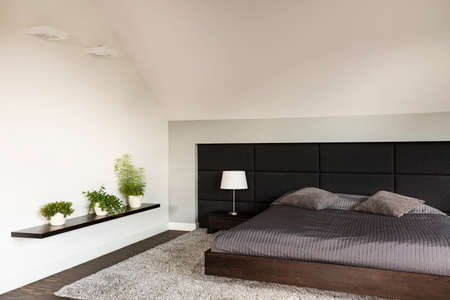 bedroom wall: Simple light bedroom in japanese style with large bed, upholstered wall, carpet, three bonsai trees standing on a wall shelf