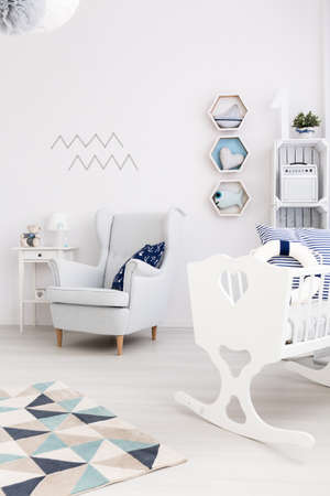 Fragment of a newborn boys room with cosy armchair and a white cradle with a lifebelt inside Stock Photo