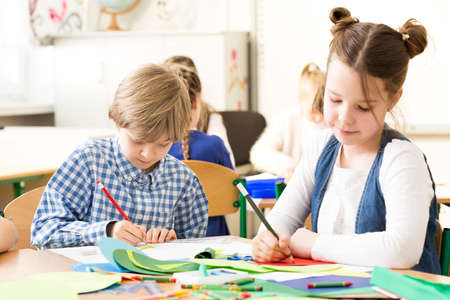 respecting: School kids concentrated on drawing during classes of art