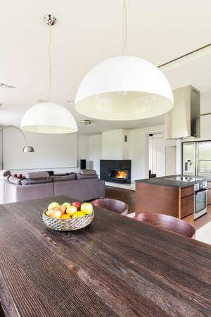 Piso abierto moderno con mesa de comedor de madera oscura y lámpara colgante blanca Foto de archivo