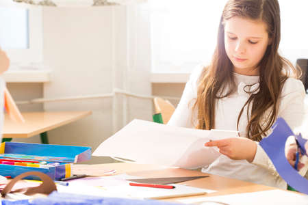 Long-haired girl in bright classroom concentrated on her sketch