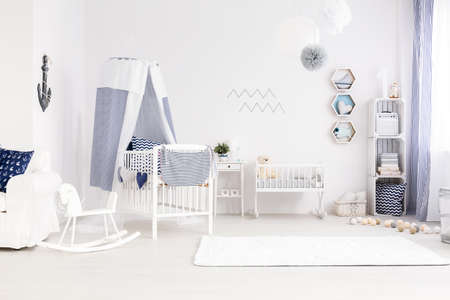 accessories horse: Very bright and pure baby room decor in marine style, with canopy cot, white cradle and carpet Stock Photo