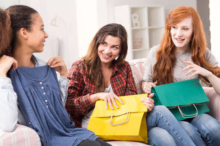 commenting: Two teenagers commenting on the blouse the third one has bought, sitting on the sofa with shopping bags on their knees Stock Photo