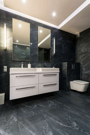 basins: New bathroom with black tiling, white cabinet, toilet, two countertop basins and two mirrors