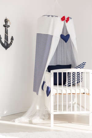 panelled: White canopy cot in marine style in a corner of a baby room illuminated with sunlight
