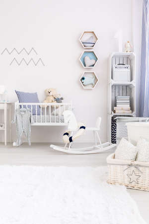 panelled: Very bright and natural baby room with white fluffy carpet, a rocking horse and a cradle
