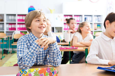 Young pupils in smart clothes sitting at desks in a classroom Stock Photo