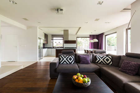 extra large: New style light living room with extra large sofa, small table, kitchen in the background