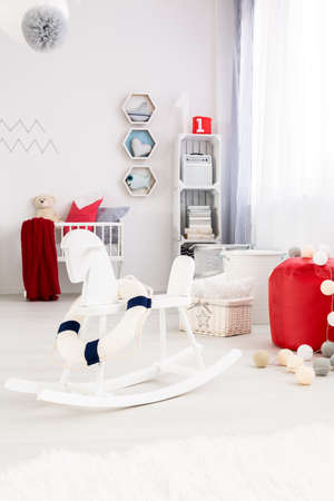 Illuminated, bright baby room furnished in white, with blue and red decorative elements