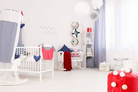 accessories horse: Very bright interior of a newborns room filled with marine decorations and white furniture Stock Photo