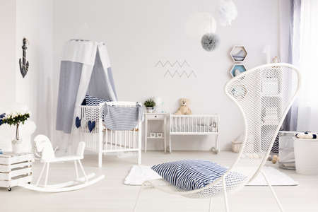 accessories horse: Bright and clean room for a newborn, with a wire armchair in the foreground and white baby room furniture